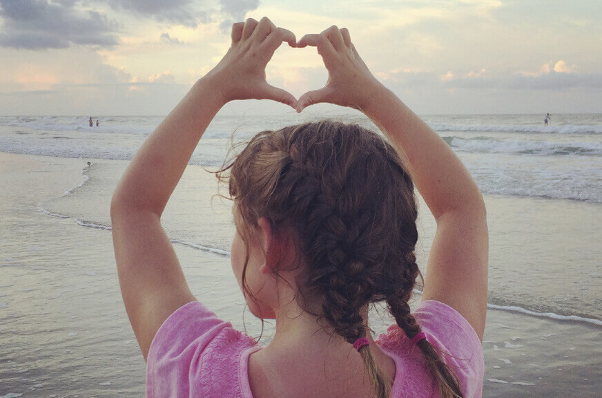 Image: Girl on the beach making a heart with her hands